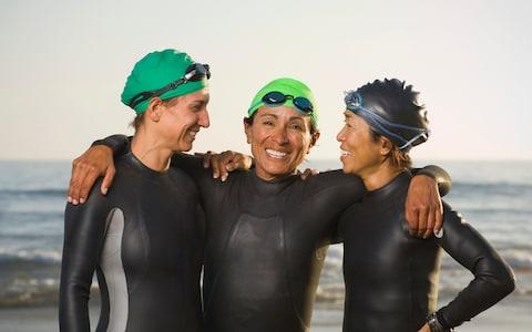 Women wearing wetsuits and goggles - Credit: Erik Isakson/Blend Images
