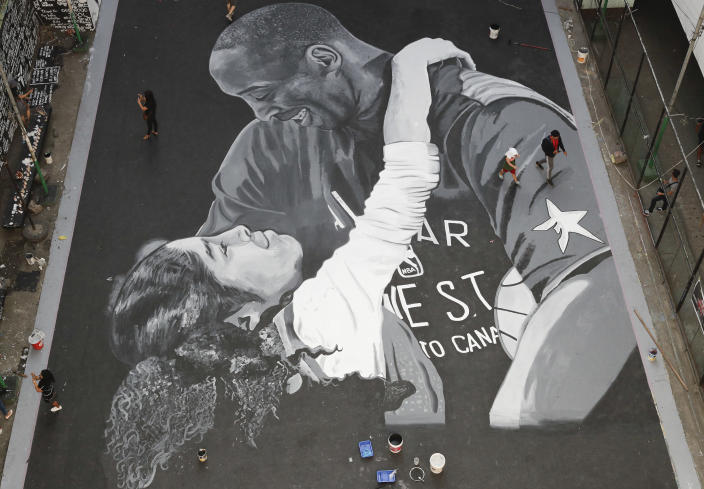 FILE - In this Jan. 28, 2020, file photo, people walk beside a giant mural of former NBA basketball player Kobe Bryant and daughter Gianna at a basketball court in Taguig, south of Manila, Philippines. Artists in this tenement building gathered and painted this image after learning of Bryant's death. Bryant, his daughter and 7 others died in a helicopter crash. (AP Photo/Aaron Favila, File)