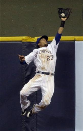 Milwaukee Brewers center fielder Carlos Gomez leaps at the wall to catch a ball hit by New York Mets' Marlon Byrd during the seventh inning of a baseball game Friday, July 5, 2013, in Milwaukee. (AP Photo/Morry Gash)