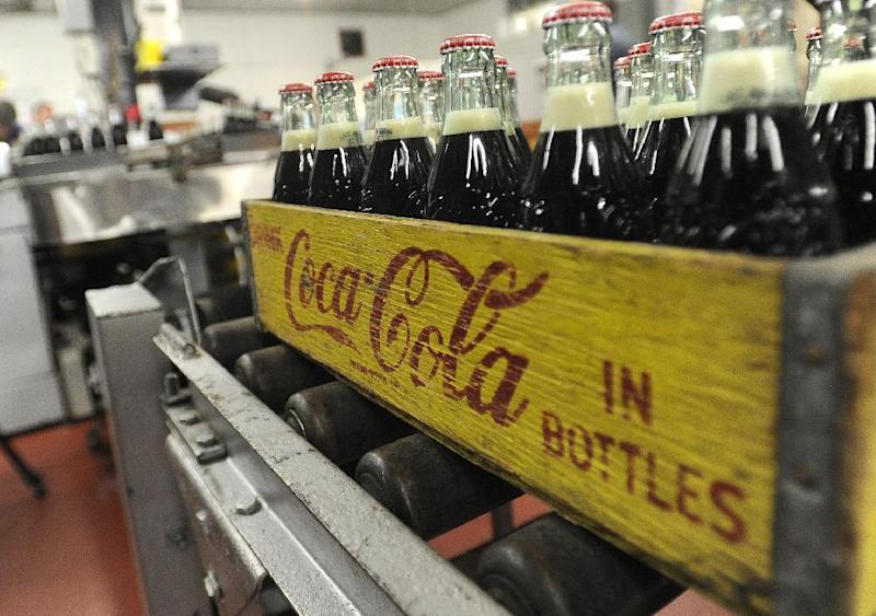 FILE - In this Tuesday, Oct. 9, 2012, photo, bottles in the last run are prepared for crates at the Coca-Cola Bottling Company in Winona, Minn. The Coca-Cola Co. says its net income rose 4 percent in the third quarter, as the world's biggest beverage maker expanded in in emerging markets and relied more heavily on sports drinks and teas for growth home. (AP Photo/Winona Daily News, Andrew Link)