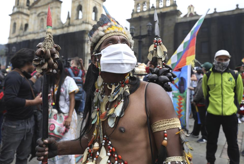 An Indigenous man, wearing a protective face mask, who is participating in a national strike, arrives to Plaza Bolivar in Bogota, Colombia, Wednesday, Oct. 21, 2020. Workers' unions, university students, human rights defenders, and Indigenous communities have gathered for a day of protest in conjunction with a national strike across Colombia. The protest is against the assassinations of social leaders, in defense of the right to protest and to demand advances in health, income and employment. (AP Photo/Fernando Vergara)