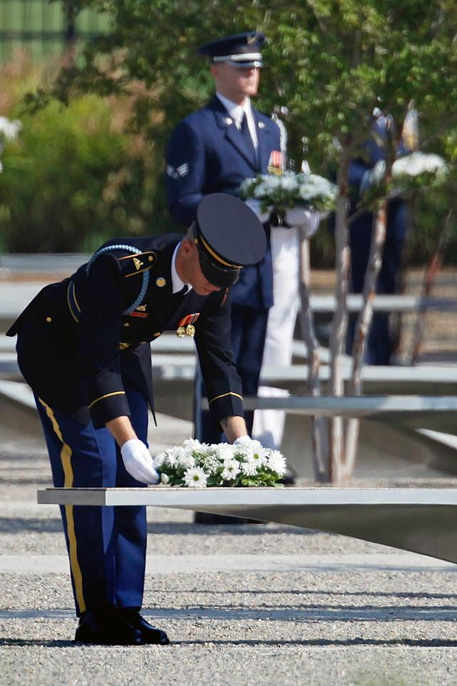 Soldiers lay wreaths at the Pentagon Memorial for each Sept. 11 victim on the benches bearing their names during the observance 10th anniversary of the September 11 attacks at the Pentagon in Washington, Sunday, Sept. 11, 2011. (AP Photo/Charles Dharapak)