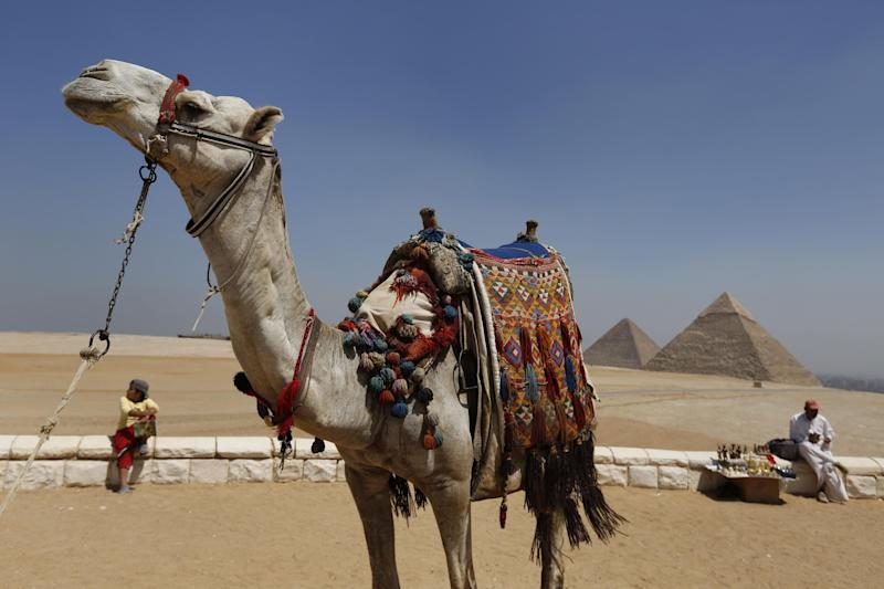 In this Saturday, Sept. 7, 2013 photo, a tourist guide sits close to his camel as a vendor waits for tourists to offer souvenirs for sale at the historical site of the Giza Pyramids, near Cairo, Egypt. Before the 2011 revolution that started Egypt's political roller coaster, sites like the pyramids were often overcrowded with visitors and vendors, but after a summer of coup, protests and massacres, most tourist attractions are virtually deserted to the point of being serene. (AP Photo/Lefteris Pitarakis)