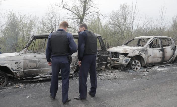 Local police officers inspect burnt-out cars after a night fight at the check point which is under the control of pro-Russian activists in the village of Bulbasika near Slovyansk, Ukraine, Sunday, April 20, 2014. At least one person was killed. Pro-Russian insurgents defiantly refused to surrender their weapons or give up government buildings in eastern Ukraine, despite a diplomatic accord reached in Geneva and overtures from the government in Kiev. (AP Photo/Efrem Lukatsky)