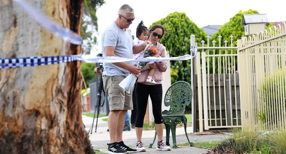 Mourners arrive to place flowers outside a property at a crime scene in Tullamarine, Melbourne