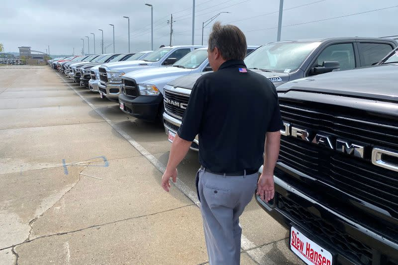 Jerry Bill, general manager of Stew Hansen Chrysler Dodge Jeep Ram, walks past a line of Ram trucks in Urbandale