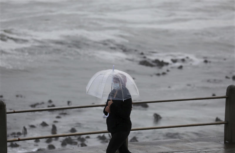 A woman walks on the promenade in stormy weather in Sea Point, Cape Town, South Africa, Friday, May 29, 2020. With dramatically increased community transmissions, Cape Town has become the center of the coronavirus outbreak in South Africa. (AP Photo/Nardus Engelbrecht)