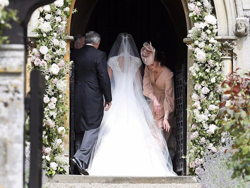 Even Pippa caught some of Kate's motherly ways when her veil needed straightening. Source: Getty