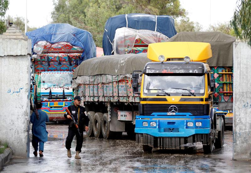 An Afghan security guard stands while supply trucks carrying containers for export line at the Customhouse in Jalalabad