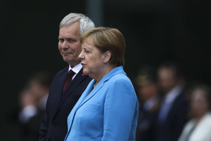German Chancellor Angela Merkel, right, and Prime Minister of Finland Antti Rinne listen to the national anthems at the chancellery in Berlin, Germany, Wednesday, July 10, 2019. Merkel's body shook visibly as she stood alongside the Finnish prime minister and listen to the national anthems during the welcoming ceremony at the chancellery. (AP Photo/Markus Schreiber)