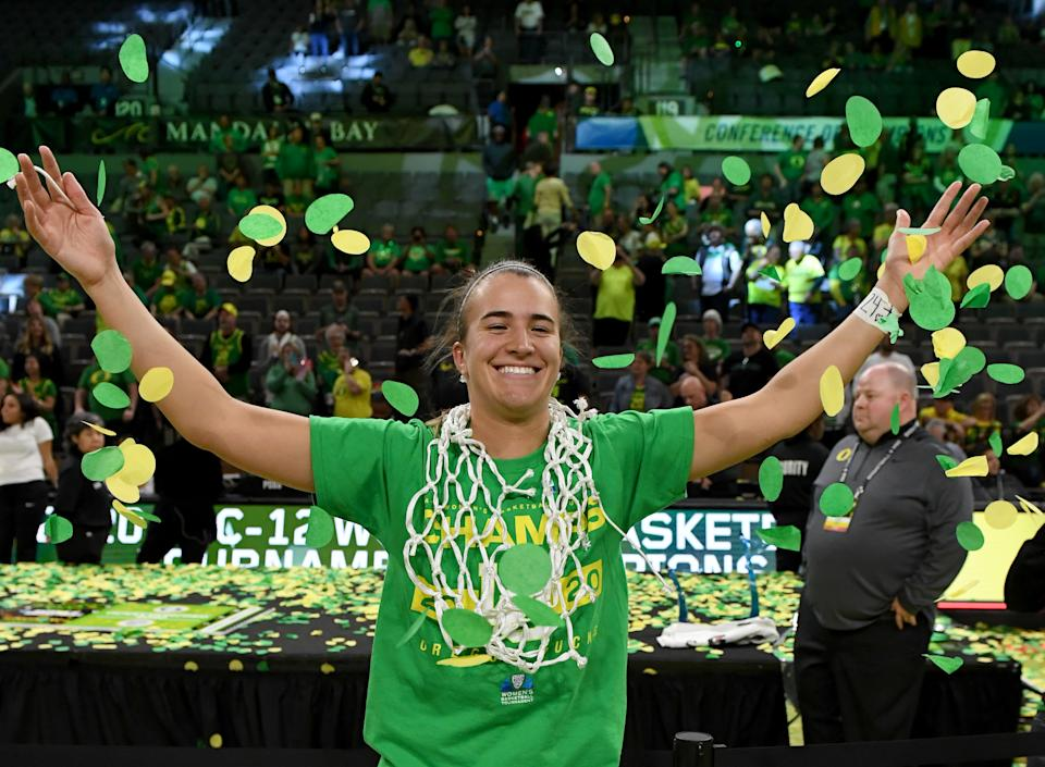 Sabrina Ionescu #20 of the Oregon Ducks wears a basketball net around her neck and throws confetti in the air as she celebrates her team's 89-56 win over the Stanford Cardinal to win the championship game of the Pac-12 Conference women's basketball tournament at the Mandalay Bay Events Center on March 8, 2020 in Las Vegas, Nevada.  (Photo by Ethan Miller/Getty Images)