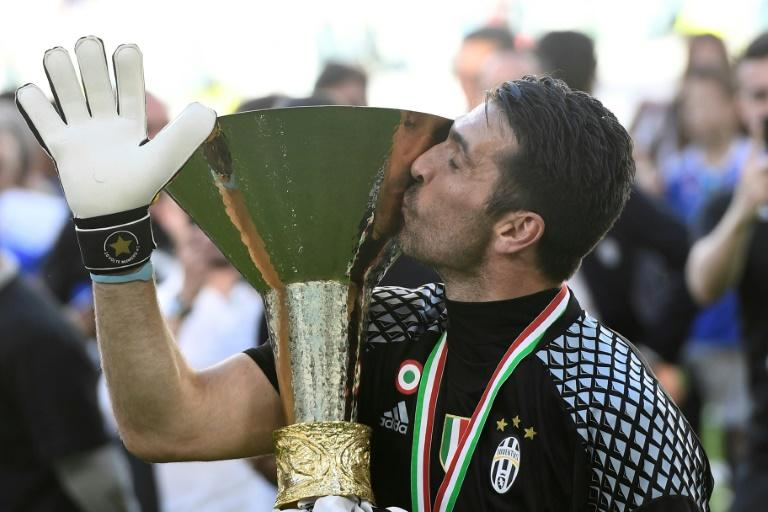 "Juventus' goalkeeper from Italy Gianluigi Buffon kisses the trophy after winning the Italian Serie A football match Juventus vs Crotone and the ""Scudetto"" at the Juventus Stadium in Turin on May 21, 2017"