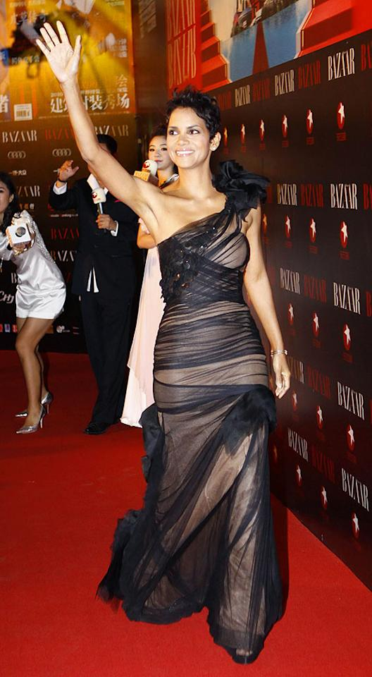 """Halle Berry looked beyond beautiful at the Shanghai Bazaar Charity Ball in a black organza Vera Wang gown, which featured a nude underlay and ruffled detail on the shoulder. Minimal makeup and subtle jewels accentuated her showstopping look. ChinaFotoPress/<a href=""""http://www.gettyimages.com/"""" target=""""new"""">GettyImages.com</a> - April 25, 2010"""