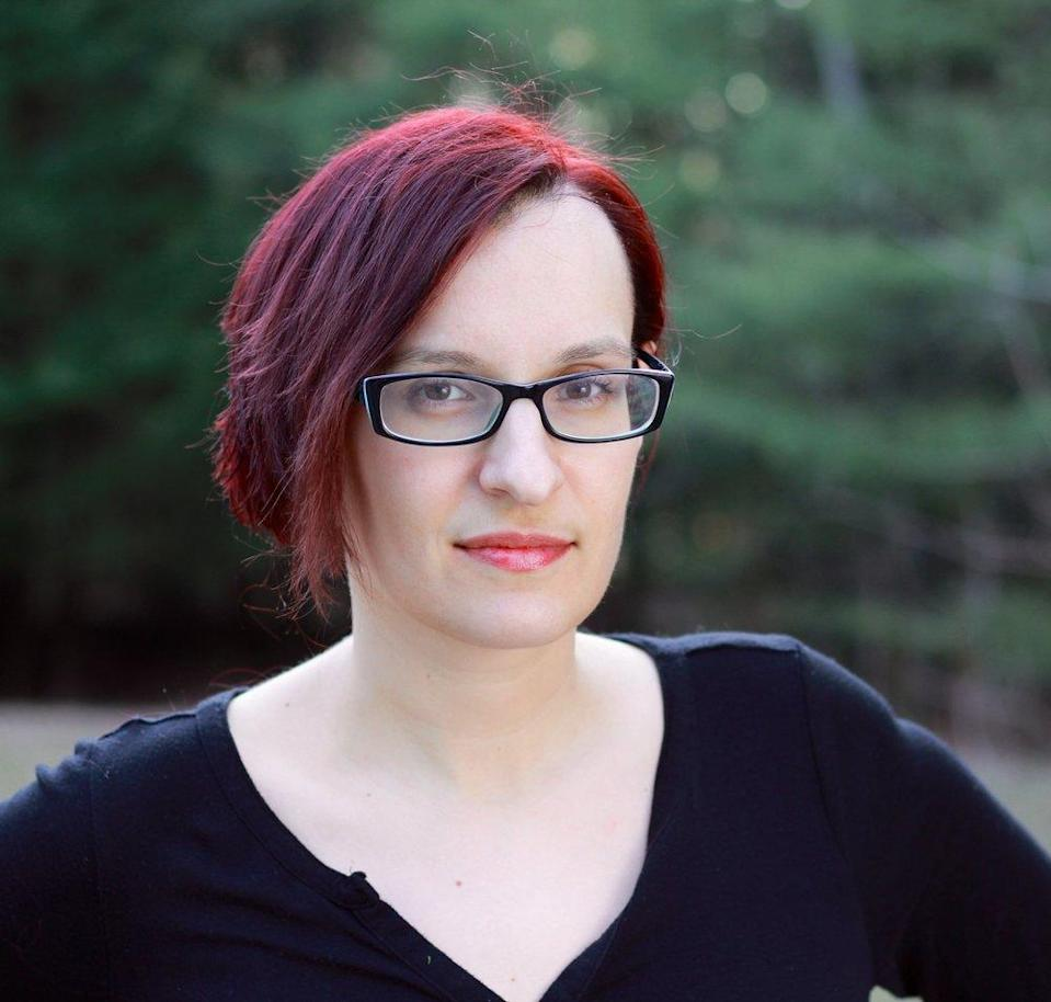 A woman with glasses and dark red hair.