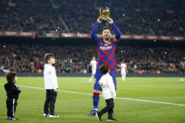 Barcelona's Lionel Messi, with his children, shows the supporters his sixth Golden Ball for the best player of the year that he was awarded earlier in the week, before a Spanish La Liga soccer match between Barcelona and Mallorca at Camp Nou stadium in Barcelona, Spain, Saturday, Dec. 7, 2019. (AP Photo/Joan Monfort)