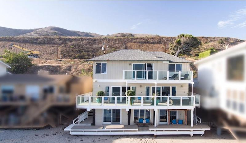 The three-story house sits on the beach in Malibu.