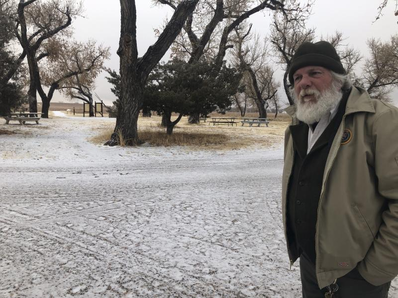 In this Dec. 27, 2019, photo, Jeff C. Campbell, a volunteer ranger at the Sand Creek Massacre National Historic Site in Eads, Colo., speaks about the history of the site. This quiet piece of land tucked away in rural southeastern Colorado seeks to honor the 230 peaceful Cheyenne and Arapaho tribe members who were slaughtered by the U.S. Army in 1864. It was one of worst mass murders in U.S. history. (AP Photo/Russell Contreras)