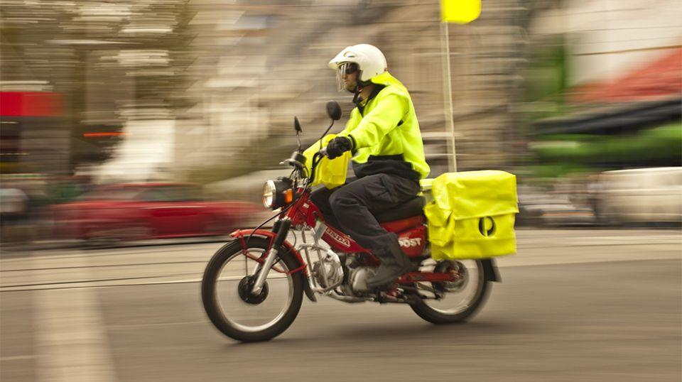 Pictured is an Australia Post postie riding a motorbike.