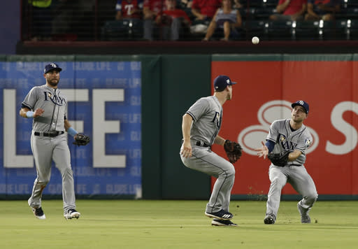 Tampa Bay Rays right fielder Brandon Lowe, on right, and second baseman Joey Wendle, center, are unable to get to the ball hit by Texas Rangers' Robinson Chorines as center fielder Kevin Kiermaier watches during the second inning of a baseball game Wednesday, Sept. 18, 2018, in Arlington, Texas. (AP Photo/Mike Stone)