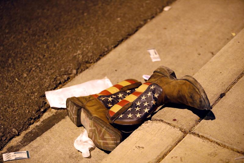 A pair of cowboy boots lies in the street outside the concert venue.