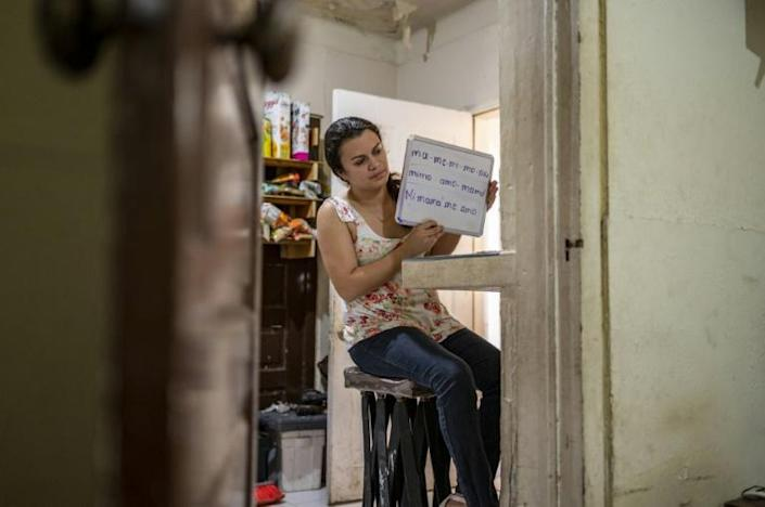 Ana Gabriela Martinez holds up a whiteboard during an online class she teaches from her home in Matamoros, Mexico