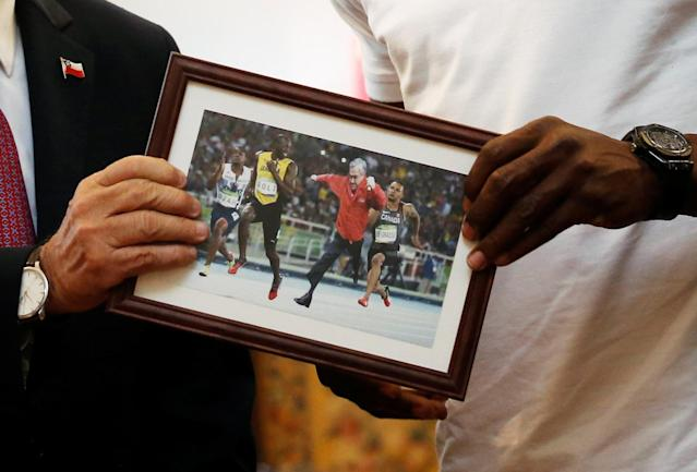 Chilean President Sebastian Pinera, presents to the former sprinter Usain Bolt, a photomontage of the President Pinera running next to him, during his visit at the government palace in Santiago, Chile April 1, 2019. REUTERS/Rodrigo Garrido