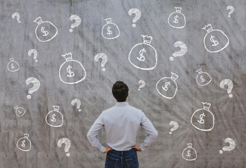 A man looking at a chalkboard covered by drawings of money bags and question marks.