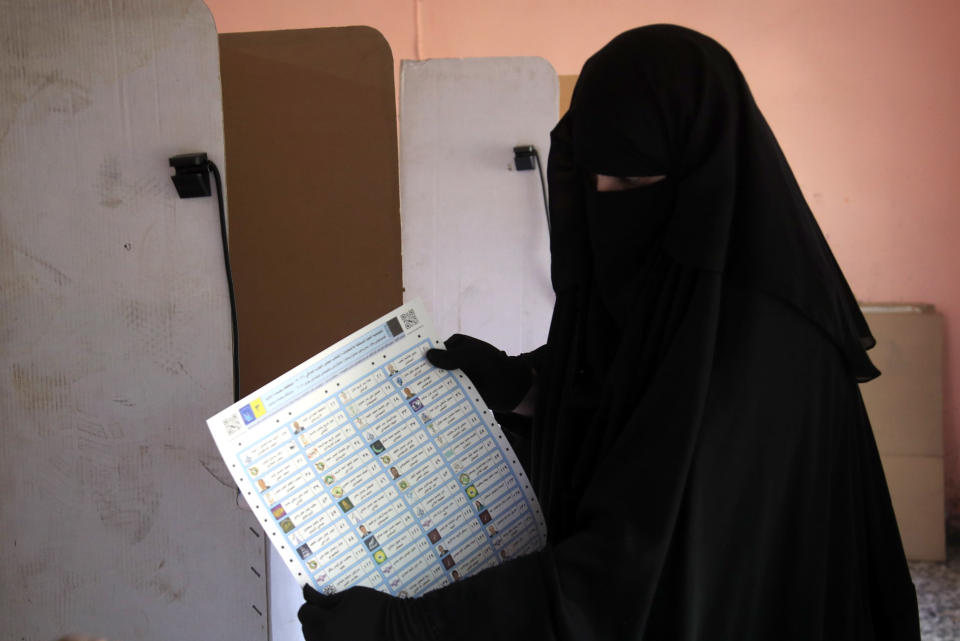 An Iraqi woman shows her ballot as she casts her vote at a polling center in Baghdad, Iraq, Sunday, Oct. 10, 2021. Iraq closed its airspace and land border crossings on Sunday as voters headed to the polls to elect a parliament that many hope will deliver much needed reforms after decades of conflict and mismanagement. (AP Photo/Hadi Mizban)