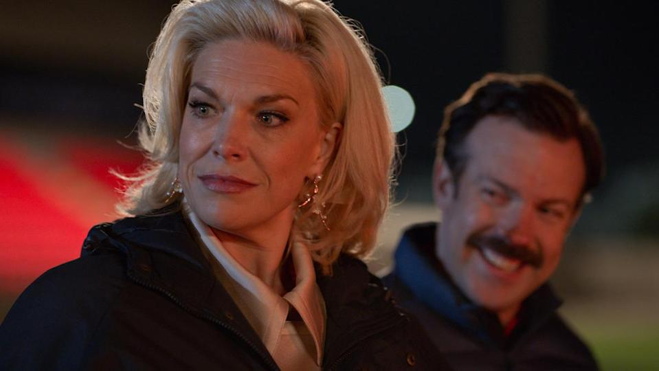 Rebecca Welton (Hannah Waddingham) smiles softly with Ted Lasso (Jason Sudeikis) in the background.