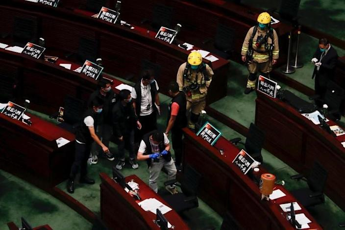 The police take photos at the chamber of the Legislative Council after pro-democracy lawmakers hurled objects during third reading on the controversial national anthem bill in Hong Kong