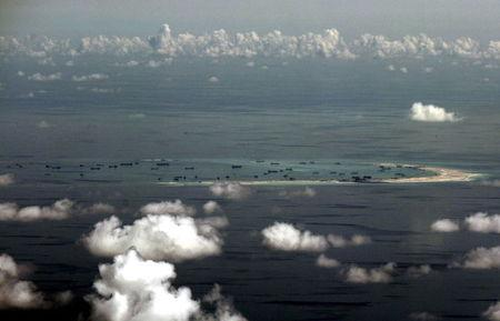 An aerial photo taken though a glass window of a Philippine military plane shows the alleged on-going land reclamation by China on mischief reef in the Spratly Islands