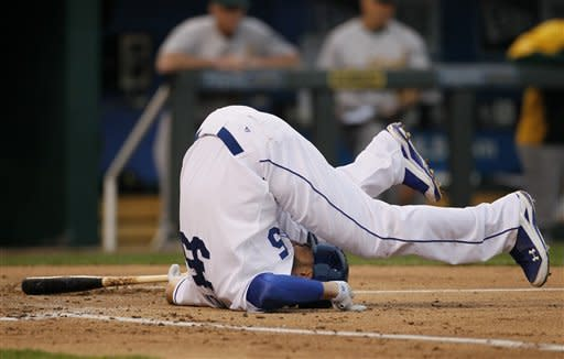 Kansas City Royals batter Eric Hosmer falls to the ground after fouling the ball off an ankle during the third inning against the Oakland Athletics in Kansas City, Mo., Thursday, Aug. 16, 2012. (AP Photo/Colin E. Braley)