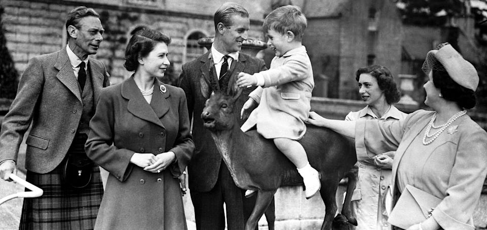 The Queen and Prince Philip with a young Prince Charles during a summer holiday in balmoral. The Royals are all smiles as the future Prince of Wales pretended to ride an animal statue.