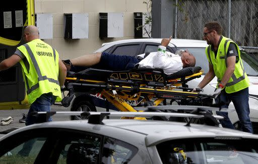 Ambulance staff take an injured man from outside a mosque in central Christchurch (AP Photo/Mark Baker)