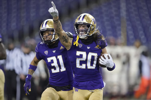 FILE - Washington's Asa Turner (20) celebrates with Kamren Fabiculanan (31) after Turner intercepted a pass in the final minute of an NCAA college football game against Oregon State in Seattle, in this Saturday, Nov. 14, 2020, file photo. Washington won 27-21. Washington has pulled out of the Pac-12 football championship game due to COVID-19 issues in the Huskies program, and Oregon will now play No. 13 USC for the conference title on Friday instead. Washington (3-1) announced Monday, Dec. 14, 2020, it is withdrawing from the championship game after determining the Huskies did not have at least 53 scholarship players available and did not meet the minimum number of scholarship athletes at specific positions.(AP Photo/Ted S. Warren, File)