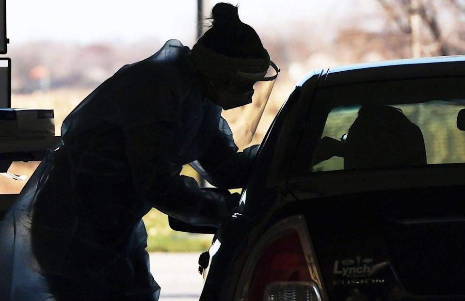 A registered nurse from TestIowa reaches into a car to take a nasopharyngeal swab from a patient at a drive-thru coronavirus testing station at Iowa State University Research Park on Nov. 13, 2020, in Ames, Iowa.
