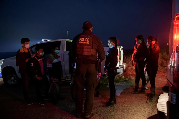 In a photo taken on March 27, 2021 unaccompanied children, immigrants who arrived illegally across the Rio Grande river from Mexico, stand at a makeshift processing checkpoint before being detained at a holding facility by border patrol agents in the border city of Roma. / Credit: ED JONES/AFP via Getty Images