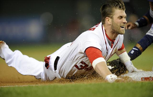 Washington Nationals left fielder Bryce Harper slides into third with a three RBI triple during the third inning of a baseball game against the San Diego Padres, Friday, April 25, 2014, in Washington. (AP Photo/Nick Wass)