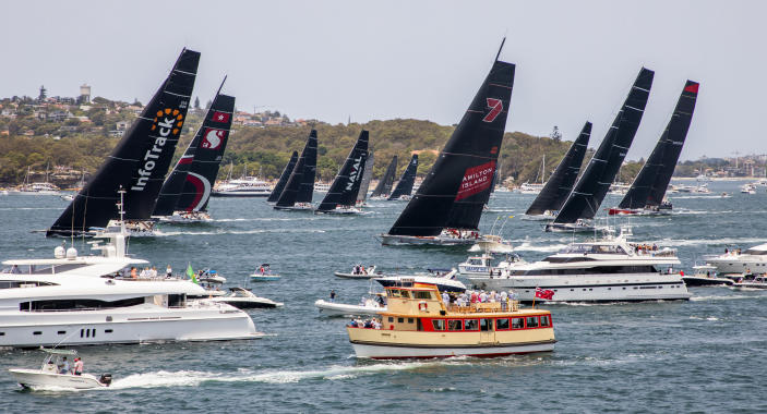 Competitors, back, race past spectators at the start of the 75th Sydney Hobart yacht race in Sydney Harbour, Thursday, Dec. 26, 2019. (Rolex/Carlo Borlenghi via AP)