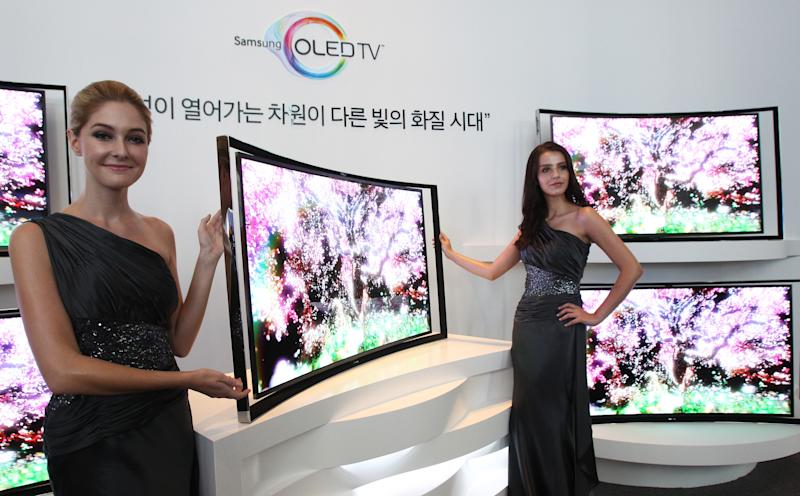Models pose with a Samsung Electronics Co.'s 55-inch curved OLED TV during a press conference at its headquarters in Seoul, South Korea, Thursday, June 27, 2013. After delays, Samsung rolled out Thursday the curved TV that uses an advanced display called OLED. The 55-inch TV will sell for 15 million won ($13,000) in South Korea, more than five times the cost of LCD televisions of the same size. (AP Photo/Ahn Young-joon)