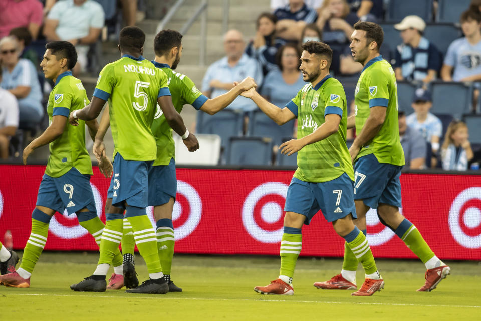 Seattle Sounders midfielder Cristian Roldan celebrates with teammates after scoring during the first half of an MLS soccer match against Sporting Kansas City, Sunday, Sept. 26, 2021, in Kansas City, Kan. (AP Photo/Nick Tre. Smith)