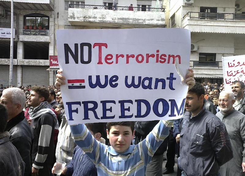FILE - In this April 22, 2011, file citizen journalism image made on a mobile phone and acquired by the AP, a Syrian boy carries a banner during an anti-government demonstration in the coastal city of Banias, Syria. The sectarian divisions burning across the rest of Syria have become physical barriers in this town on the Mediterranean coast, with soldiers manning sandbagged checkpoints dividing its Sunni Muslim southern neighborhoods from those of the Alawite and Christians in the north. Yet even after a mass killing of Sunnis in a village outside Banias in May, a tenuous truce keeps this town of 50,000 people locked in a frigid, divided peace in hopes the chaos engulfing the rest of the country will pass them by.(AP Photo, File)