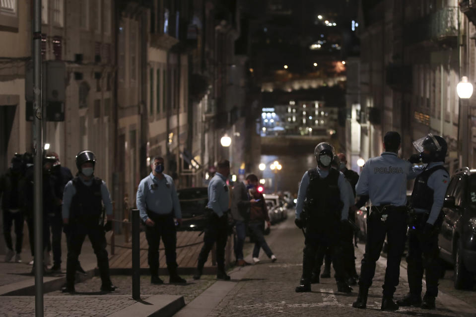 Police officers patrol a street leading to the Douro river bank where Manchester City supporters gathered, in Porto, Portugal, Saturday, May 29, 2021. English clubs Manchester City and Chelsea played the Champions League soccer final in Porto on Saturday evening. (AP Photo/Luis Vieira)