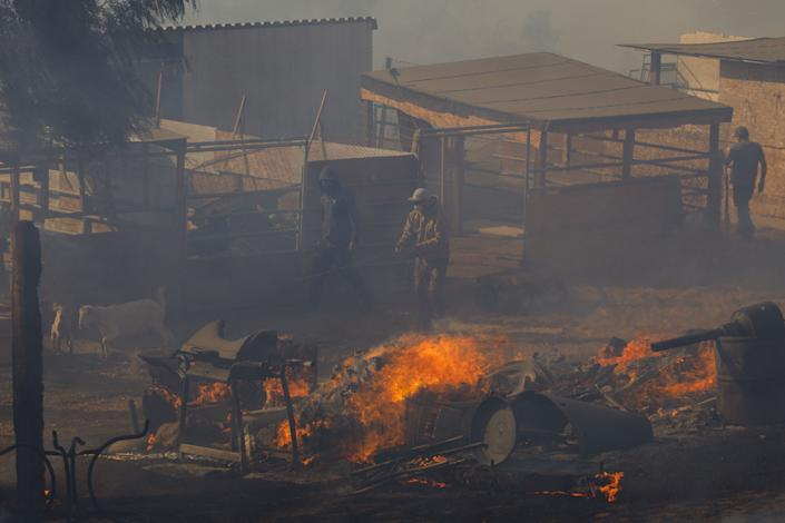 Workers try to extinguish smoldering embers on a ranch during the Easy Fire in Simi Valley, Calif. on Oct. 30, 2019. (Photo: Patrick T. Fallon/Bloomberg via Getty Images