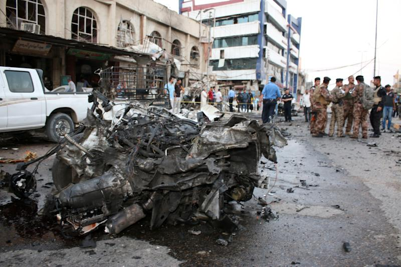 Iraqis gather at the site of a car bombing on Al-Saadi street in the center of the southern city of Basra, on July 5, 2014 (AFP Photo/Haidar Mohammed Ali)