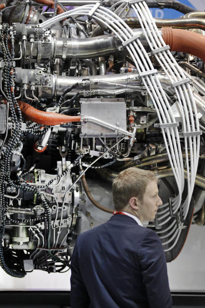 A visitor watches General Electric the GEnx jet engine, powering Boeing 787 Dremliner, during the 50th Paris Air Show at Le Bourget airport, north of Paris, Wednesday June 19, 2013. (AP Photo/Remy de la Mauviniere)