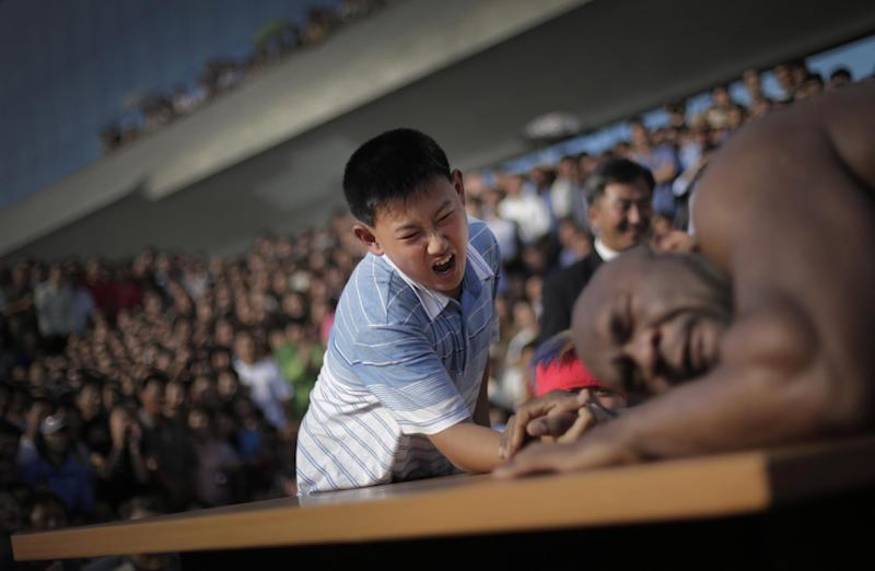 "In this Friday, Aug. 29, 2014 photo, a North Korean boy arm wrestles with former NFL player Bob ""The Beast"" Sapp in Pyongyang, North Korea.  In an oddball attempt at sports diplomacy with North Korea, a group of about 20 mixed martial artists from around the world, including former NFL player Bob ""The Beast"" Sapp, traveled to Pyongyang last week to engage in arm-wrestling and tug-of-war competitions with local children. (AP Photo/Wong Maye-E)"