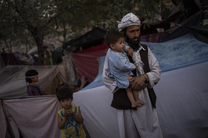 A displaced Afghan family waits for food donations at a camp for internally displaced persons in Kabul, Afghanistan, Monday, Sept. 13, 2021. (AP Photo/Bernat Armangue)