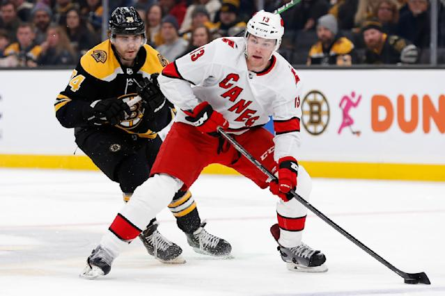 Carolina Hurricanes' Warren Foegele (13) handles the puck in front of Boston Bruins' Jake DeBrusk (74) during the first period of an NHL hockey game in Boston, Tuesday, Dec. 3, 2019. (AP Photo/Michael Dwyer)