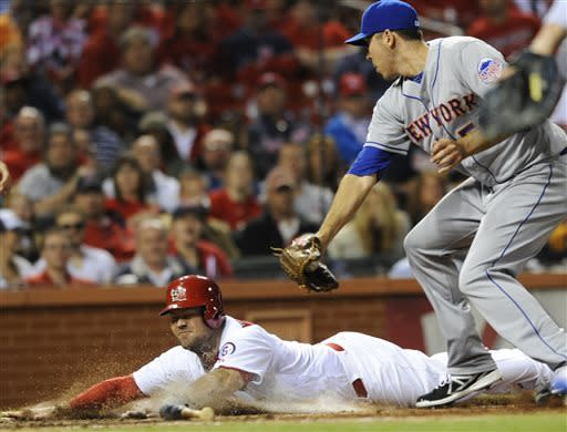 St. Louis Cardinals' Ty Wiggington, left, scores under the tag of New York Mets' Scott Rice, in the seventh inning in a baseball game Monday, May 13, 2013, at Busch Stadium in St. Louis. (AP Photo/Bill Boyce)
